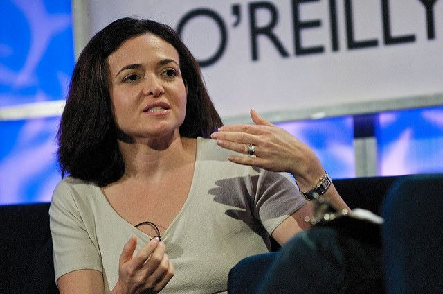 Sheryl Sandberg sitting while being interviewed on a stage.